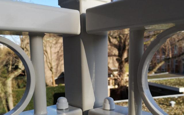 Detail van balkonhek op maat in de kleur wit met kunststof dopjes