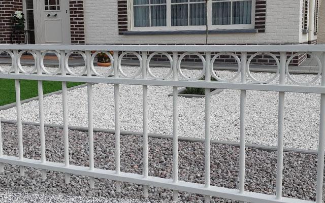 Tuinhek voor een huis in de kleur wit als afscheiding tussen de tuin en de stoep